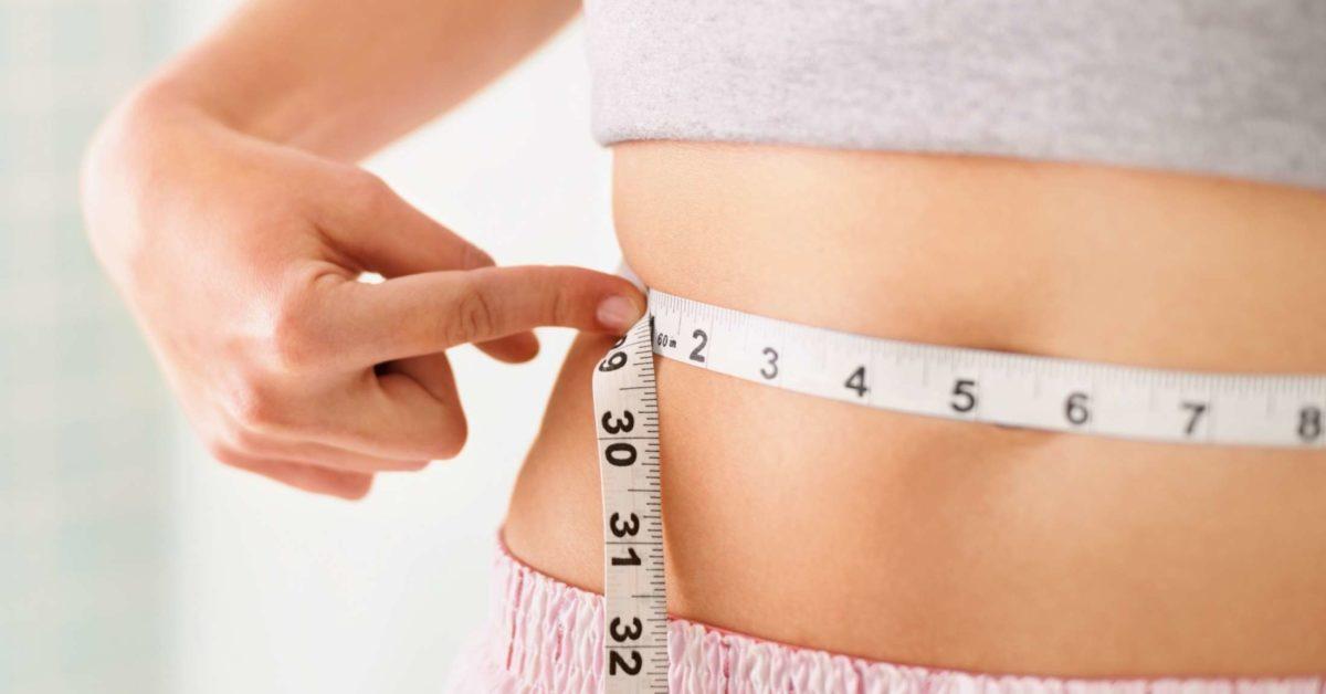 Woman measures her waist